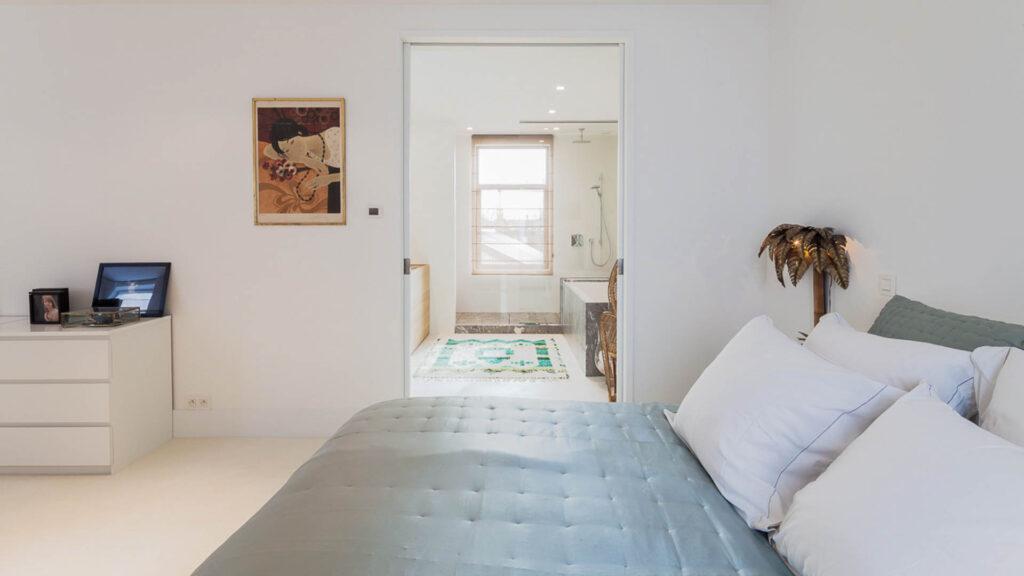 De ruime slaapkamer met aanpalende dressing en badkamer